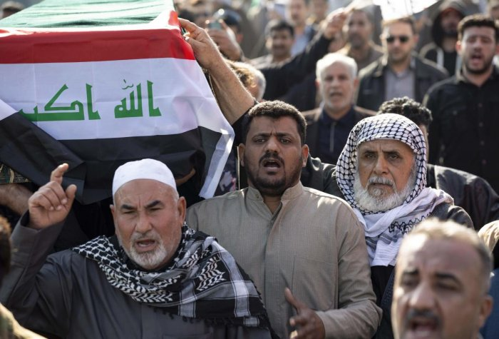 Iraqis carry a mock coffin as they march in a symbolic funeral procession for senior Iraqi military figure Abu Mahdi al-Muhandis, in the southern city of Basra
