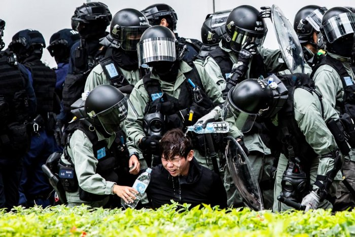 A man (C) has pepper spray washed from his his face by police after being detained during a clearance operation after a demonstration against parallel trading in Sheung Shui in Hong Kong on January 5, 2020. (AFP photo)