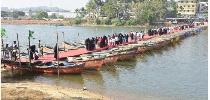 People cross the temporary bridge made of boats to reach Rahmania Dargah Masjid Shariff at Adyar-Kannur on Sunday. DH PHOTO