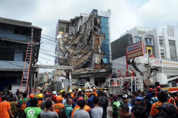 A crowd gathers to watch rescuers as they search a five-storey building after part of the structure collapsed in Jakarta on January 6, 2020. (AFP Photo)