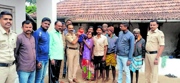 Police and forest department officials hand over Nityashree, the lost child, to her parents. DH Photo