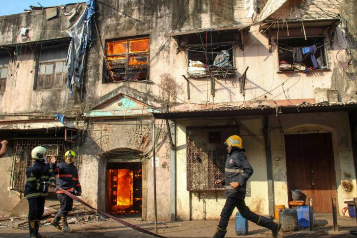 Fire-fighters try to douse the fire which broke out in A building, at Kamathipura in Mumbai. (PTI Photo)