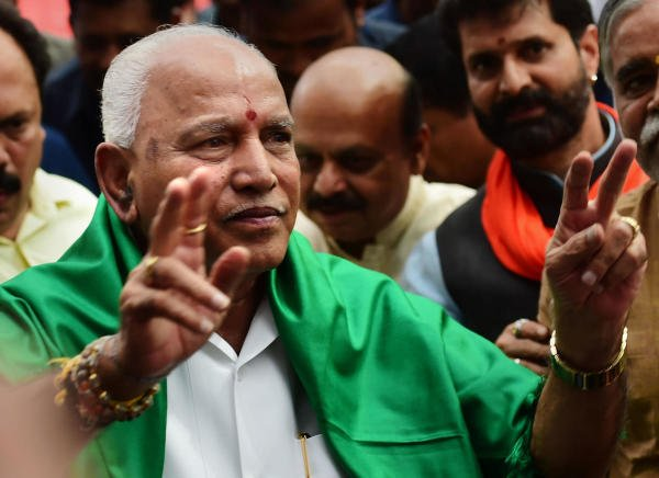 BJP leader B S Yeddyurappa flashes the victory sign before taking oath as Karnataka Chief Minister, at Raj Bhavan in Bengaluru, Friday, July 26, 2019. (Credit: PTI Photo/Shailendra Bhojak)