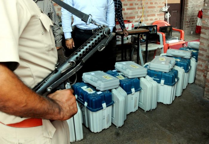 Amritsar: Police officers stand guard near Electronic Voting machines (EVM) and Voter Verifiable Paper Audit Trail (VVPAT) machines before they are distributed among polling officials, on the eve of seventh and last phase of Lok Sabha elections, Amritsar,
