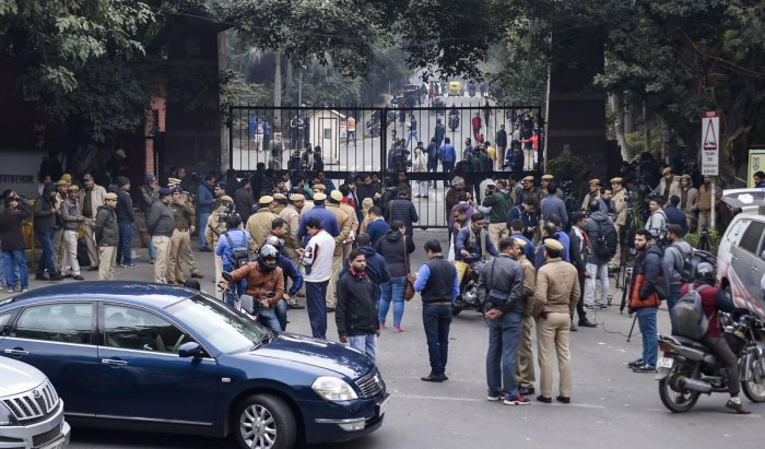 Police personnel guard as students and media are also seen at the main gate of the Jawaharlal Nehru University (JNU), in New Delhi, Monday, Jan. 6, 2020. A group of masked men and women armed with sticks, rods and acid allegedly unleashed violence on the