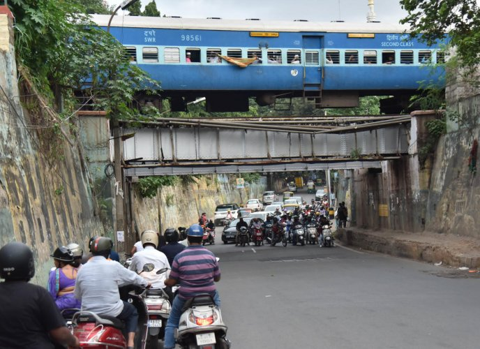 Two-wheelers wait patiently under the railway overbridge for the train to pass at Seshadripuram. DH Photo/Janardhan B K