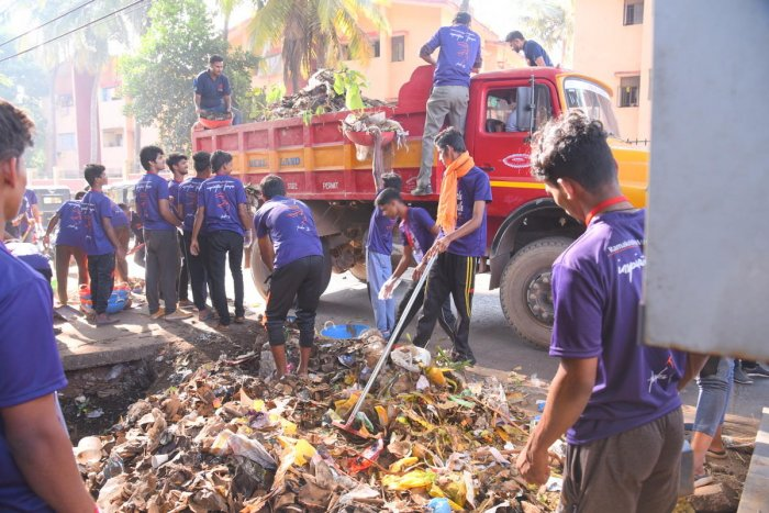 Volunteers clear garbage dumped beside the road near the Mangaluru Central Railway Station on Sunday.