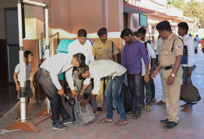 The police check backpack of a passenger at Davanagere railway station on Friday. DH Photo