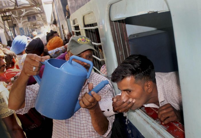 A man offers drinking water to a train passenger at a railway station on a hot day in Patiala on May 28, 2019. PTI