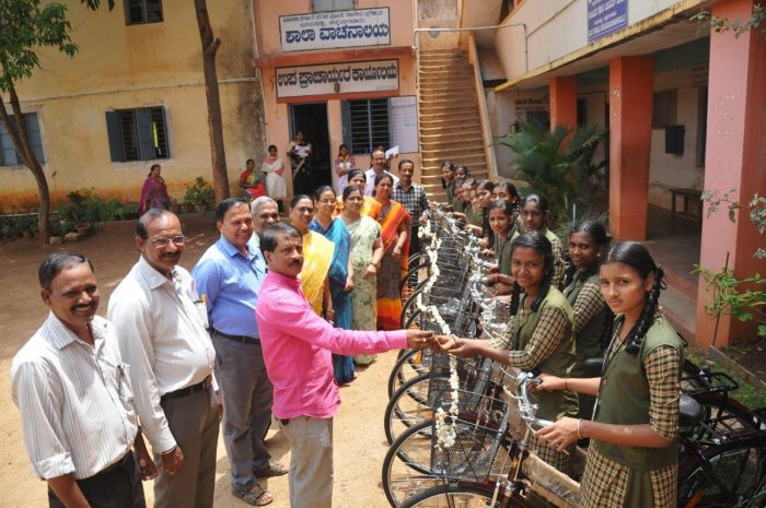 Government Girls High School Development and Monitoring Committee president Varasiddhi Venugopal distributes cycles to the students on Tuesday.