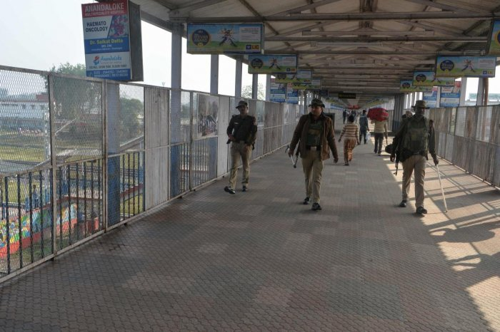 Members of the railway special protection force (RPSF) patrol on a quiet pedestrian bridge at New Jalpaiguri Railway station after several trains were cancelled due to protests against India's new citizenship law in Siliguri on December 17, 2019. (AFP Pho