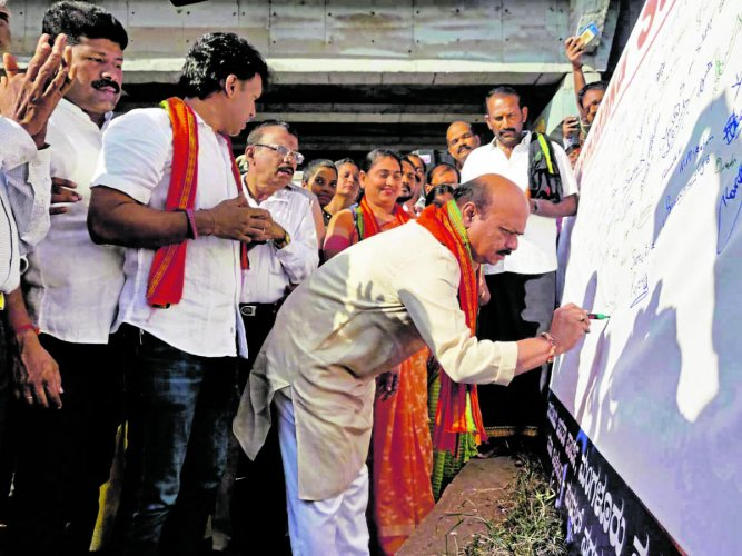 Home Minister Basavaraj Bommai takes part in a signature campaign in favour of CAA at Surathkal on Tuesday.