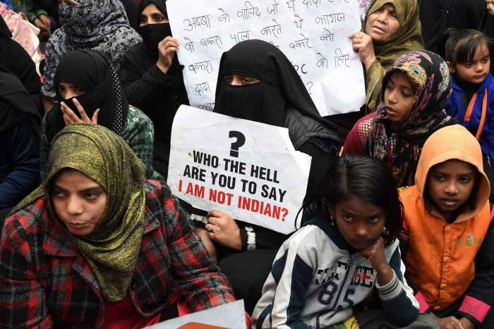 Protesters hold placards as they listen to speakers in Shaheen Bagh area in Delhi. (PTI Photo)