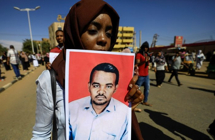 A Sudanese woman carries a portrait of the teacher Ahmed al-Khair as she celebrates after the sentencing of 27 members of the national intelligence service to death by hanging over the killing of a teacher in detention in February during protests that led to the overthrow of former president Omar al-Bashir. (Reuters Photo)