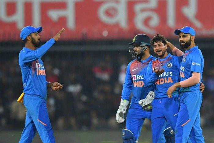 India's cricket team captain Virat Kohli (R) and Kuldeep Yadav (C) celebrate the wicket of Sri Lanka's Avishka Fernando (unseen) during the second T20 international cricket match of a three-match series between India and Sri Lanka at the Holkar Cricket St