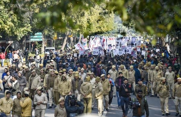 Police personnel walk in front of JNU students' protest march from Mandi House to HRD Ministry, demanding removal of the university vice-chancellor, at Ferozeshah Road in New Delhi, Thursday, Jan. 9, 2020. (PTI Photo/Ravi Choudhary)