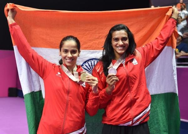 Women's singles gold medalist Saina Nehwal and silver medalist PV Sindhu pose for photographs during the medal ceremony at the Commonwealth Games 2018, in Gold Coast, Australia on Sunday. (PTI Photo)