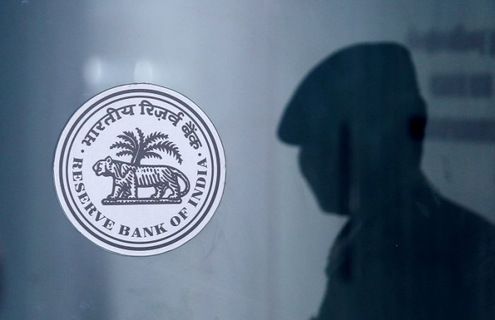 A security guard's reflection is seen next to the logo of the Reserve Bank Of India (RBI) at the RBI headquarters in Mumbai, India. (PTI Photo)
