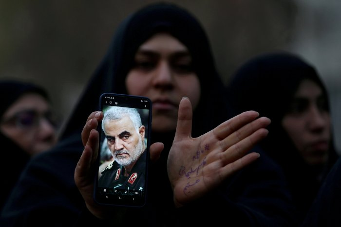 An Iranian woman shows a photo of the late Iranian Major-General Qasem Soleimani, during a protest against the killing of Soleimani, head of the elite Quds Force, and Iraqi militia commander Abu Mahdi al-Muhandis. (Reuters Photo)