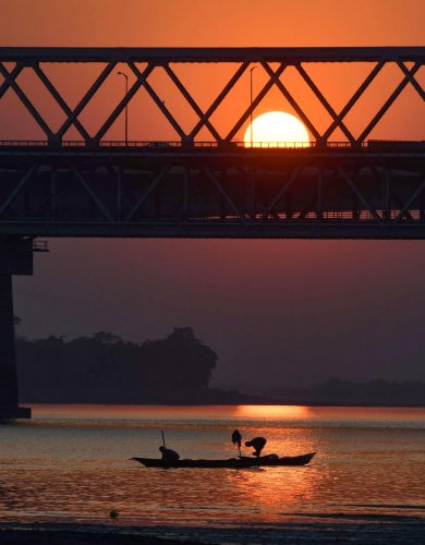 Fishermen row their boat on the Brahmaputra river during sunset in North Guwahati