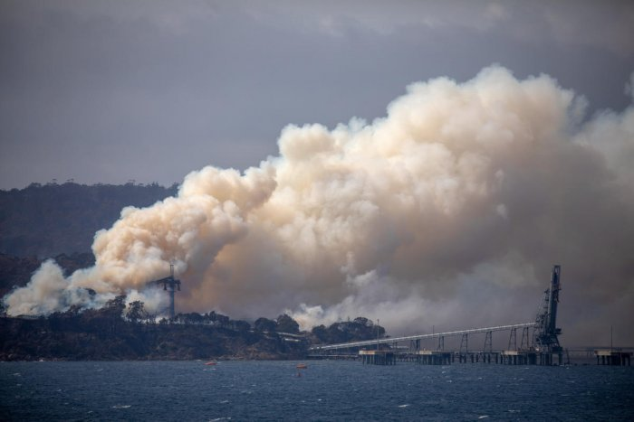 Smoke rises from the Eden Woodchip Mill, from a fire that has been blazing for days, in Eden. Reuters