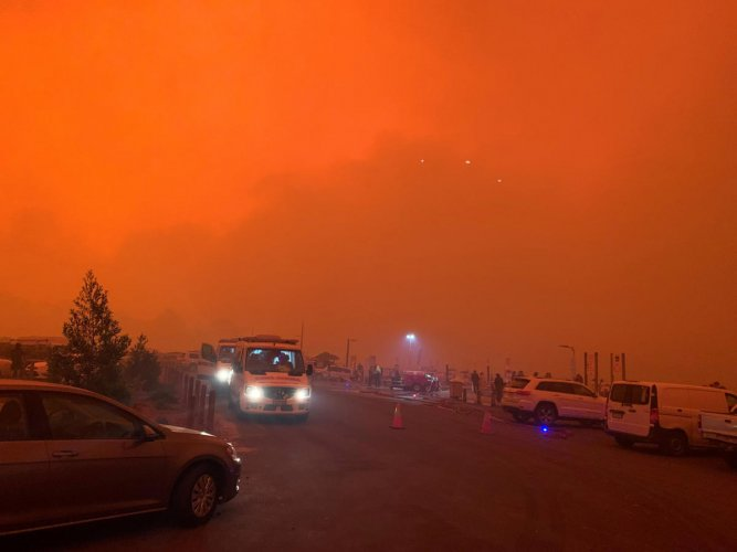 """As many as four thousand people are trapped on the foreshore of the encircled seaside town of Mallacoota, as smoke turned day to night and the authorities said nearby fires were causing extreme thunderstorms and """"ember attacks"""". Photo/Reuters"""