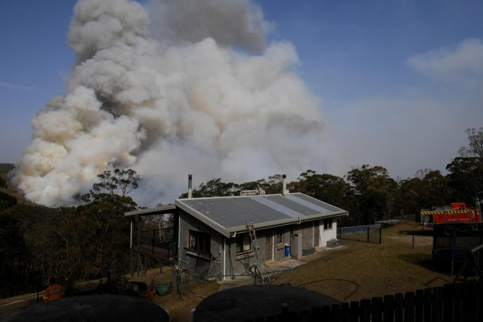 NSW Rural Fire Service crews watch on as a fire burns in bushland close to homes at Penrose in the NSW Southern Highlands, south of Sydney