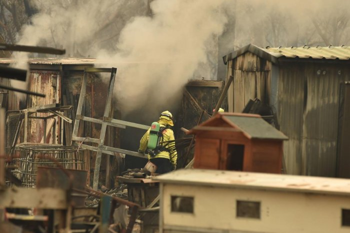 Firefighters tend to a burning property caused by bushfires in Bargo, southwest of Sydney. Photo/AFP