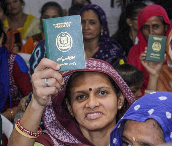 Ahmedabad: Hindu refugees who migrated from Sindh province of Pakistan display their passports as they support the Citizenship Amendment Act in Ahmadabad. The Gujarat Legislative Assembly on Friday passed a resolution congratulating the Prime Minister and the Union Home Minister for securing the passage of the Citizenship (Amendment) Act. (PTI Photo)