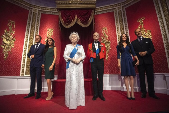 The figures of Britain's Prince Harry and Meghan, Duchess of Sussex, left, in their original positions next to Queen Elizabeth II, Prince Philip and Prince William and Kate, Duchess of Cambridge, at Madame Tussauds in London. (AP Photo)