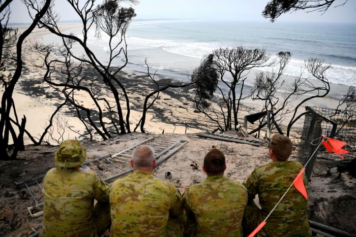 Soldiers sit on a beach amongst burnt trees where people had previously taken shelter during a fire on New Year's Eve in Mallacoota, Australia. (Reuters Photo)