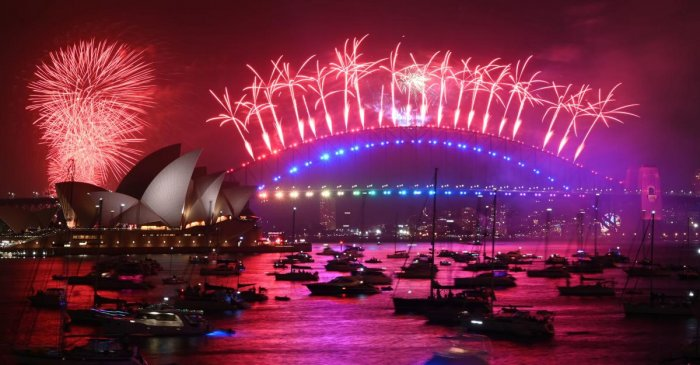 New Year's Eve fireworks erupt over Sydney's iconic Harbour Bridge and Opera House (L) during the fireworks show on January 1, 2020. AFP