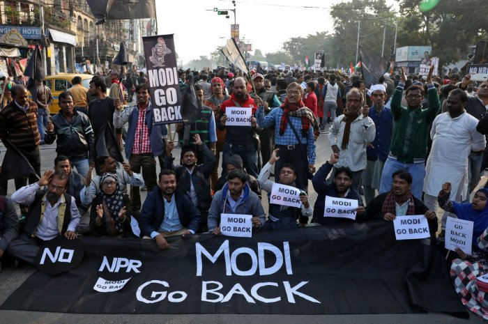 Demonstrators hold a banner and placards during a protest against the visit of India's Prime Minister Narendra Modi to the state and against a new citizenship law, in Kolkata. (Reuters photo)