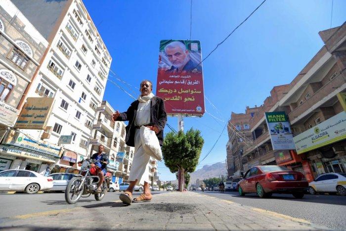 A Yemeni man walks beneath a poster of slain Iranian military commander Qasem Soleimani in the capital Sanaa, on January 8, 2020. (AFP Photo)