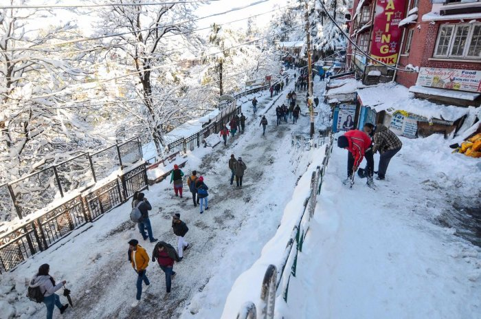 People walk on a snow-covered road after heavy snowfall in Shimla. (PTI Photo)