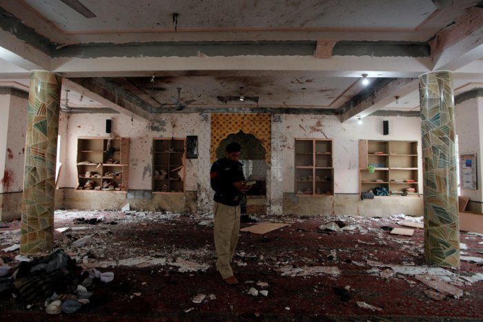 A police officer stands amidst the damages as he is surveying and collecting evidence from the site of the bomb blast in a mosque in Quetta. (REUTERS Photo)
