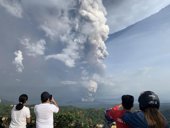 People take photos of a phreatic explosion from the Taal volcano as seen from the town of Tagaytay in Cavite province, southwest of Manila