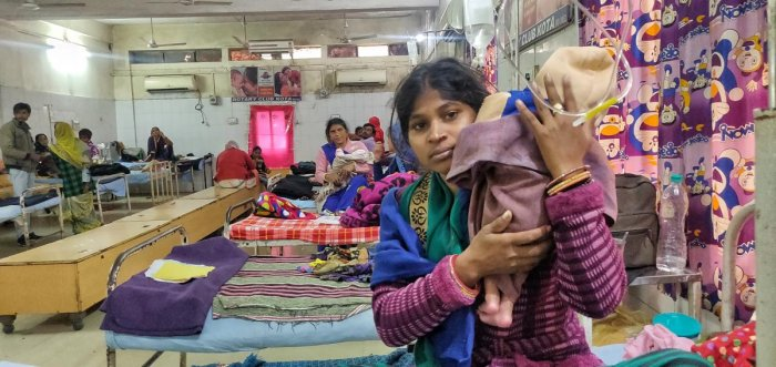 A mother holding her baby inside the general ward of the paediatrics department at the J K Lon Hospital in Kota, Rajasthan. The kin of patients wait outside the hospital, which is being renovated. (Credit: DH Photo)