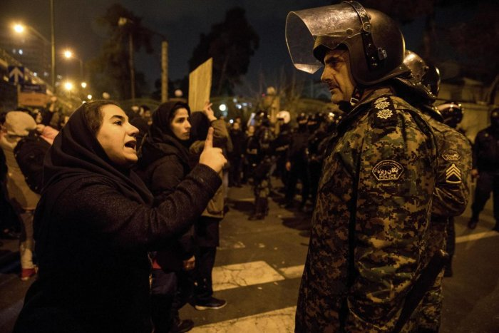 In this Saturday, Jan. 11, 2020 photo, released by Iranian Students' News Agency, ISNA, a woman attending a candlelight vigil to remember the victims of the Ukraine plane crash, talks to a policeman and asks for his sympathy, at the gate of Amri Kabir University in Tehran, Iran. Credit: AP