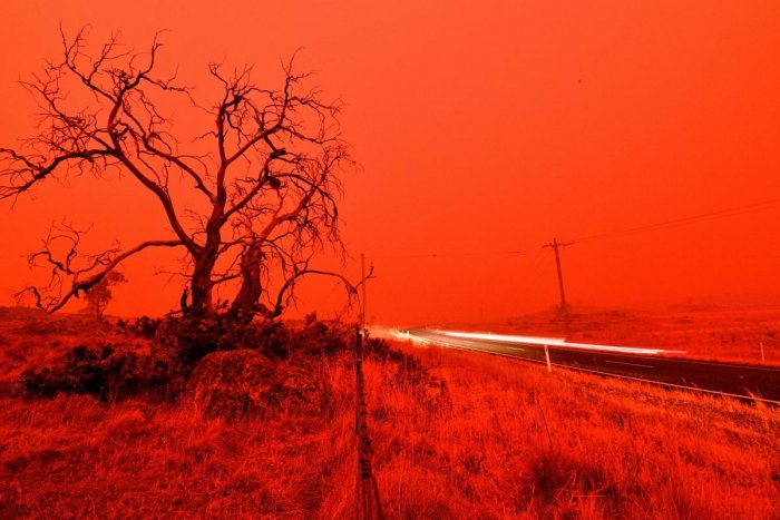 A long exposure picture shows a car commuting on a road as the sky turns red from the smoke of the Snowy Valley bushfire on the outskirts of Cooma. (AFP PHOTO)