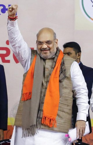 Union Home Minister Amit Shah raises his fist at a function in Ahmedabad, Saturday, Jan 11, 2020. (PTI Photo)