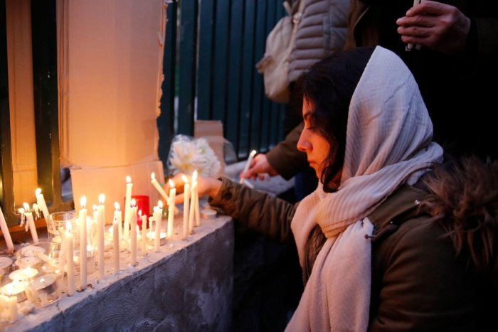 An Iranian lights candles for the victims of Ukraine International Airlines Boeing 737 during a gathering in front of the Amirkabir University in the capital Tehran. (AFP PHOTO)