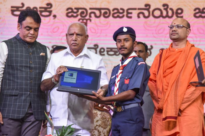 Chief Minister B S Yediyurappa hands over a laptop to a student during the launch of free laptop scheme on the occasion of National Youth Day in Bengaluru on Sunday. Deputy Chief Minister C N Ashwath Narayan and Mangalanathananda Swami of Ramakrishna Mutt