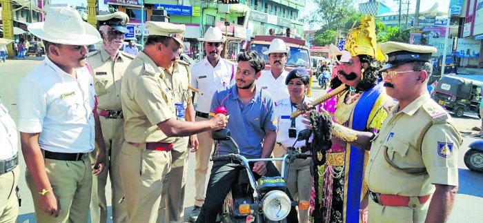 Police personnel handover a rose to a traffic violator during an awareness programme organised as a part National Road Safety Week in Kushalnagar on Sunday.