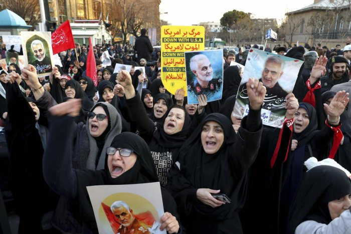 Protesters chant slogans while holding up posters of Gen. Qassem Soleimani during a demonstration in front of the British Embassy in Tehran, Iran, Sunday, Jan. 12, 2020. (AP Photo)