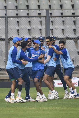 Team-mates share a light moment with Hardik Pandya who joined the Indian team's training session ahead of the first ODI against Australia at the Wankhede Stadium in Mumbai on Monday. PTI