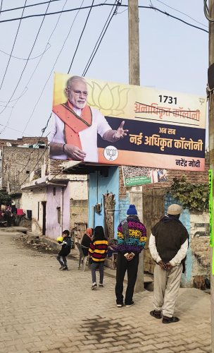 A poster of Narendra Modi on regularisation of unauthorised colonies is seen at a colony in New Delhi, Sunday, Dec. 29, 2019. The BJP have kick-started their campaign for the 2020 Delhi Assembly elections. (PTI Photo)