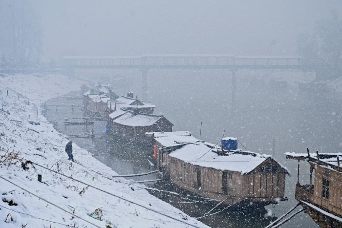 A man walks towards by house boats on the banks of the River Jhelum during snowfall in Srinagar. (AFP Photo)