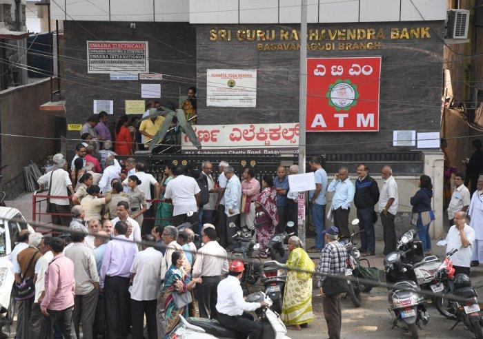 Depositors in front of the Sri Guru Raghavendra Co-operative Bank in Basavanagudi in Bengaluru on Monday. DH Photo/Srikanta Sharma R