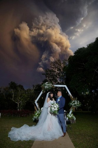 A couple attends their wedding ceremony as Taal Volcano sends out a column of ash in the background in Alfonso, Cavite, Philippines, January 12, 2020.